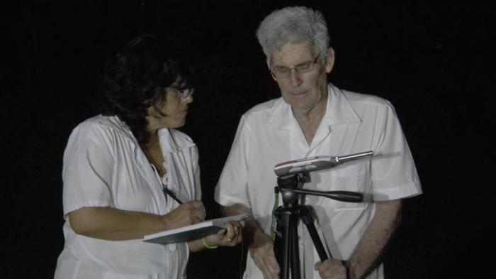 A doutora Yamile González Sánchez, chefa de departamento no Centro de Epidemiologia e Saúde Ambiental, e o doutor em Ciências Físicas, Carlos Barceló Pérez, realizam medições de ruído ambiente em horário noturno.